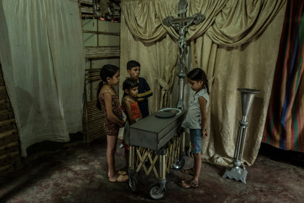 Children view the body of their 17-month old cousin, Kenyerber Aquino Merchán, who died of heart failure caused by severe malnutrition, in San Casimiro, Venezuela, on Aug. 21..jpg