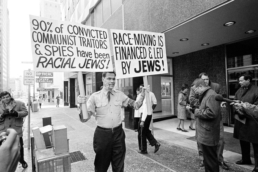3 The American Nazi Party leader George Lincoln Rockwell carries placards as he picketed a building in Dallas on January 29, 1966, to test a city law against picketing by groups such as his - Fred Kaufman.jpg