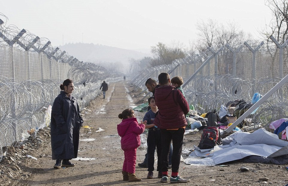A family of refugees wait in the no-man's-land area at the border which is guarded by barbed wire fences. Macedonia has closed its border with Greece, causing a bottleneck among those travelling the Balkan route.jpg
