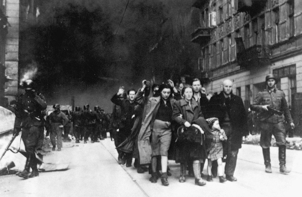 Stroop Report original caption Forcibly pulled out of dug-outs. Captured Jews are led by German troops to the assembly point for deportation. Picture taken at Nowolipie street, near the intersection with Smocza.jpg
