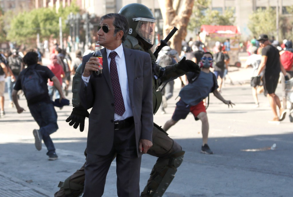 A man drinks a Frucola as a policeman chases demonstrators during a protest against Chile's government, in Santiago, Chile, on December 4, 2019.jpg
