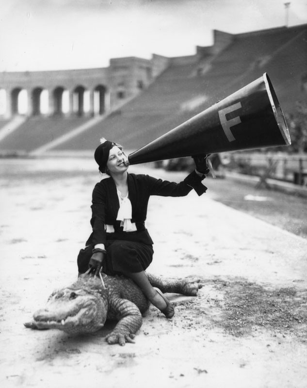 A woman riding an alligator in the Los Angeles Memorial Coliseum.  The alligator is evidently the team mascot, c 1930s (via Los Angeles Public Library).jpg