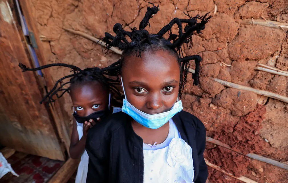 3500.jpgMartha Apisa, 12, and Stacy Ayuma, 8, pose for a photograph outside their house after plaiting their hair with a style designed to emulate the prickly appearance of the Covid-19 virus..jpg