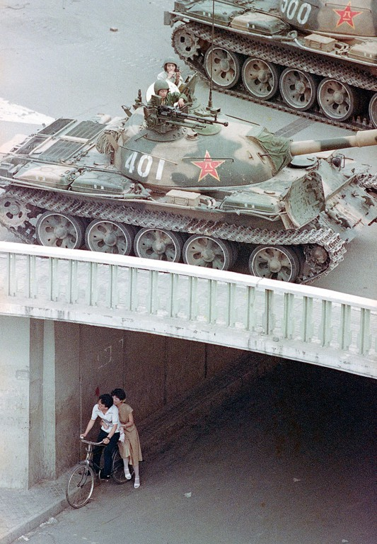 A Chinese couple on a bicycle take cover beneath an underpass as tanks deploy overhead in eastern Beijing, on June 5, 1989, Liu Heung Shing.jpg