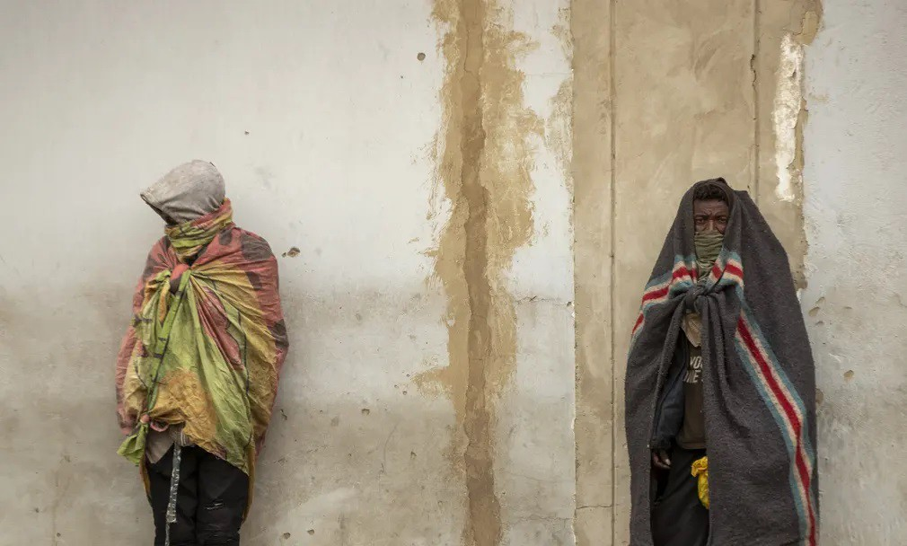 Homeless men stand against the wall on a street of downtown Johannesburg..jpg